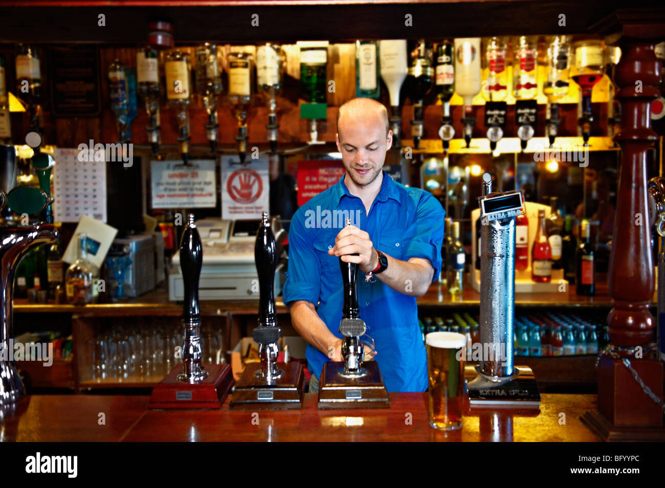 Barman standing behind bar in pub - Stock Image