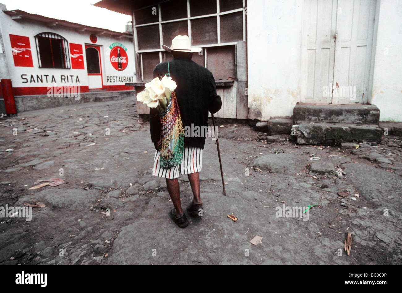 Man walks home with lilies in Santiago Atitlan, Guatemala - Stock Image