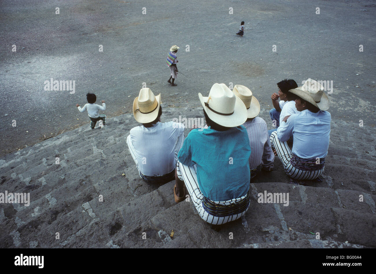 Men sit on church steps and watch passers by in Santiago, Atitlan, Guatemala - Stock Image