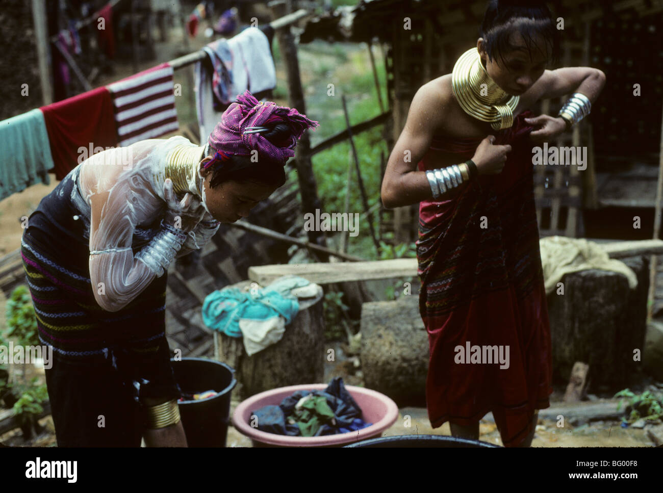 Two Burmese refugee long neck women of the Pa Dong Tribe take an open air bath in their village of Nai Soi near - Stock Image
