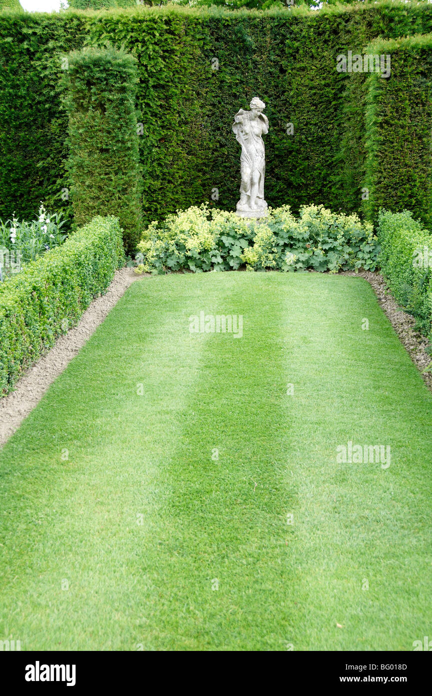 A stone statue in a garden setting - Stock Image