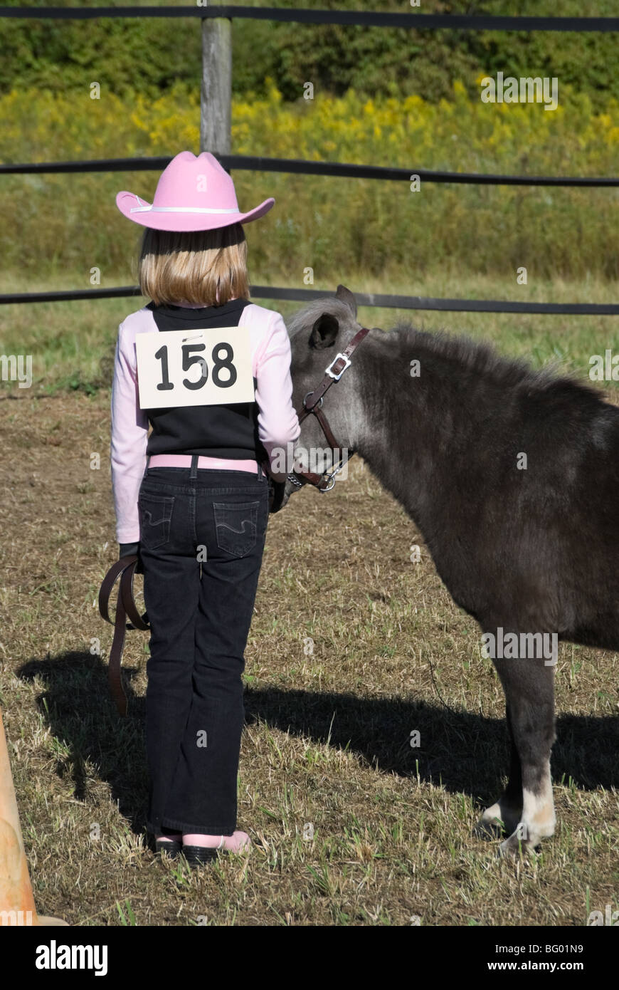 Young girl with pink boots and cowboy hat competing in a horse show halter  class with a fuzzy gray miniature horse. 494793effe94