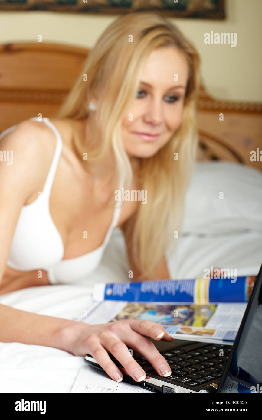 Young women looks at travel brochures while lying on bed - Stock Image