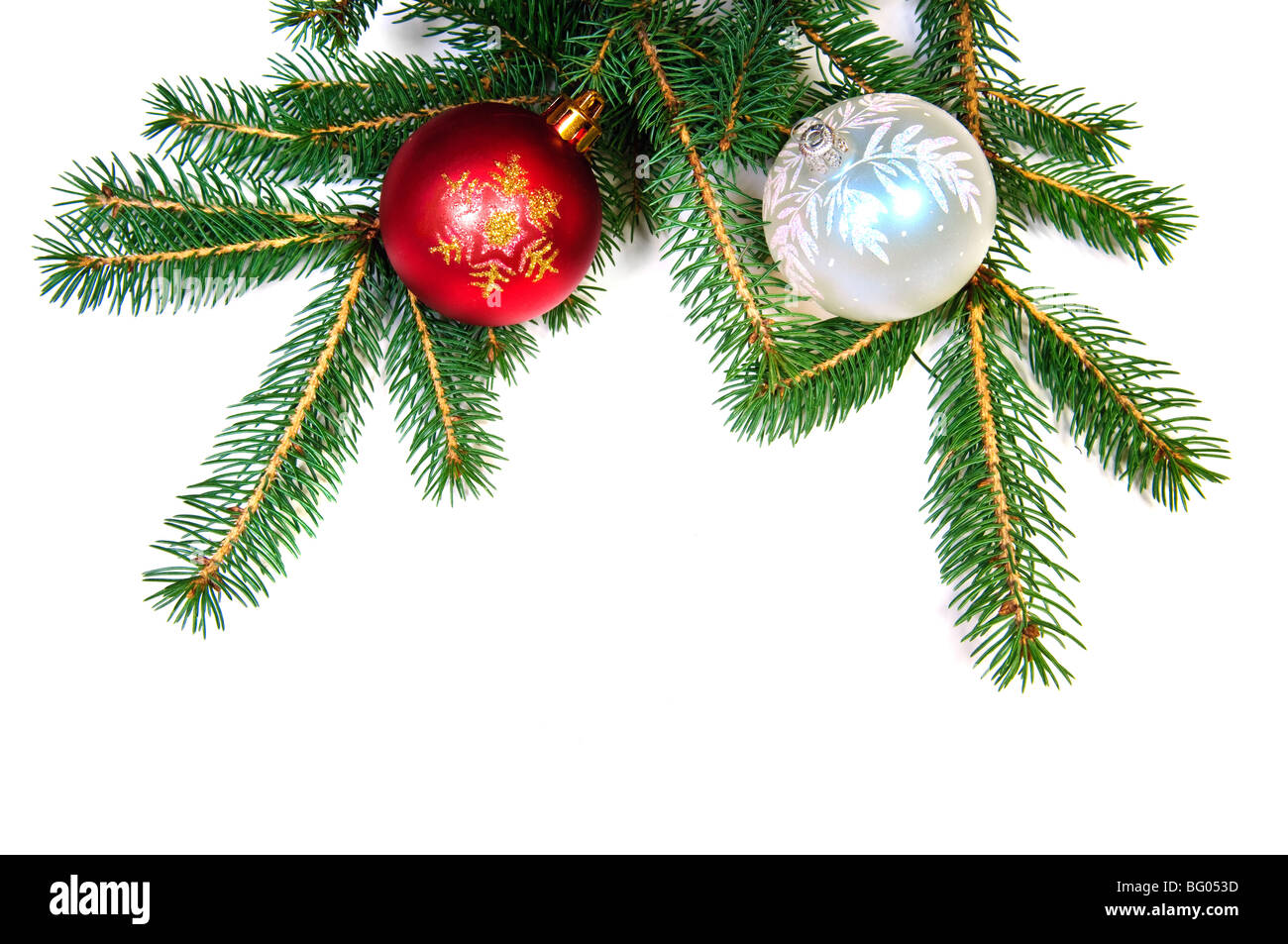 Christmas balls on fir tree branch on white background - Stock Image