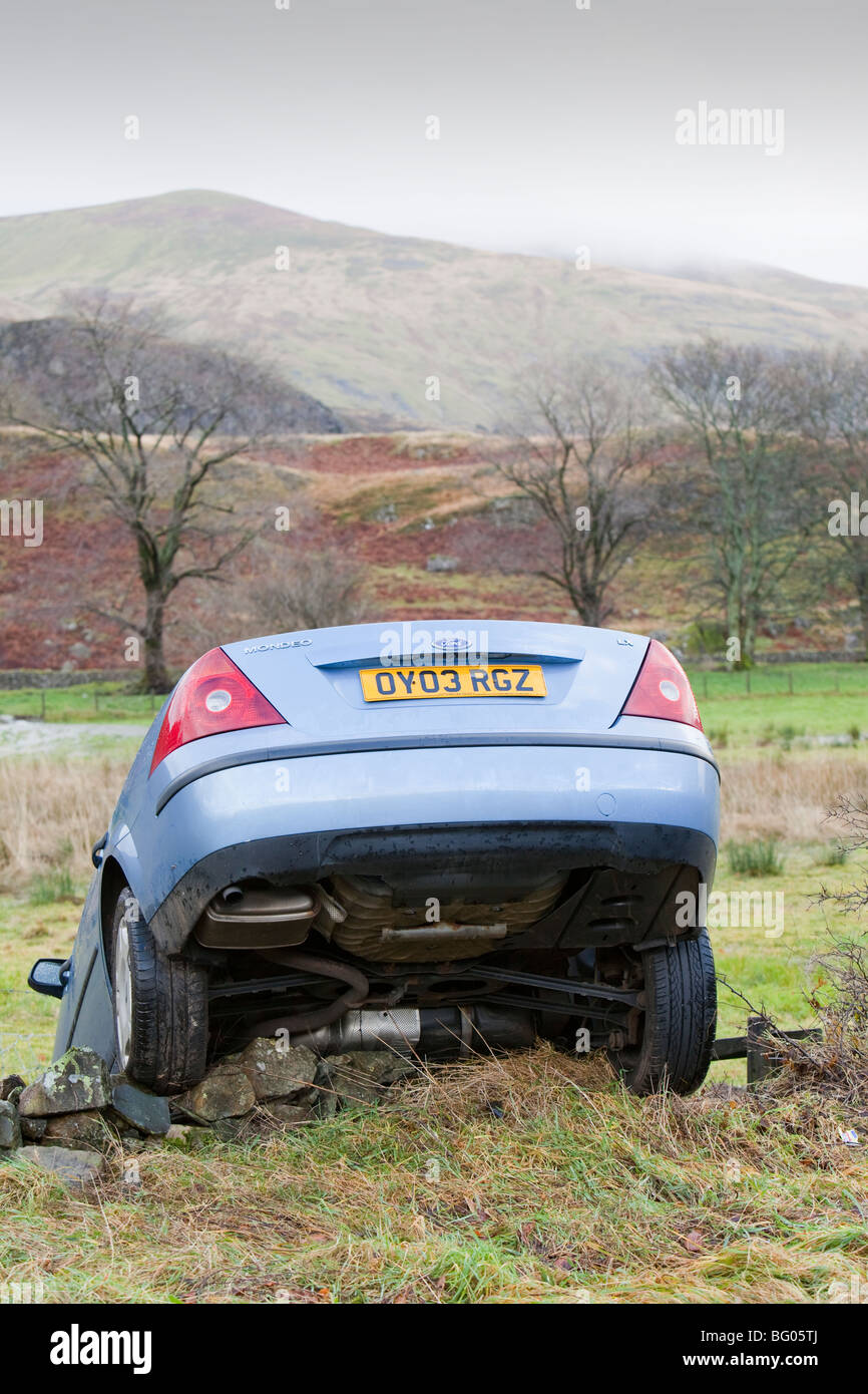 A car that crashed off the road in flood waters near Keswick, Cumbria, UK. - Stock Image