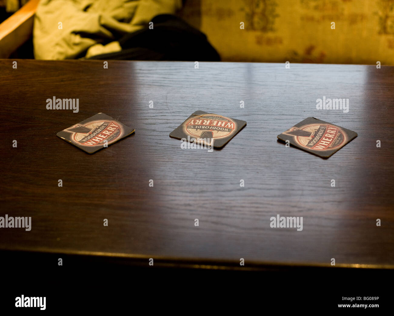 Three beer mats on a table in a pub in Essex. - Stock Image