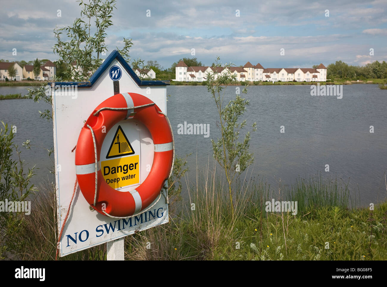 Life saving belt beside Cotswold water and warning against swimming - Stock Image