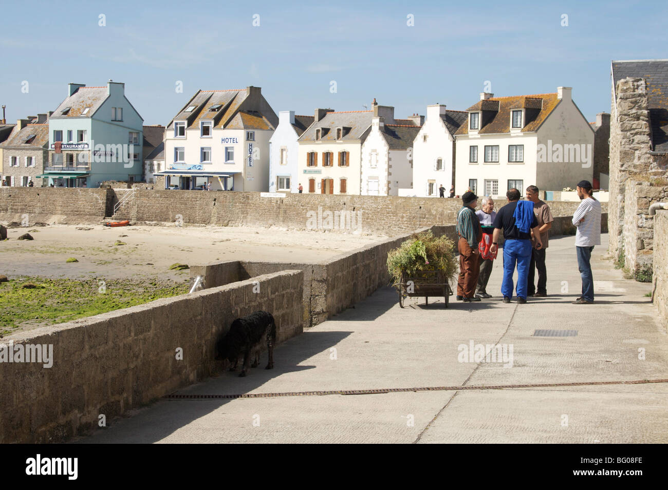 Locals on harbour front, Ile de Sein, Brittany, France, Europe - Stock Image