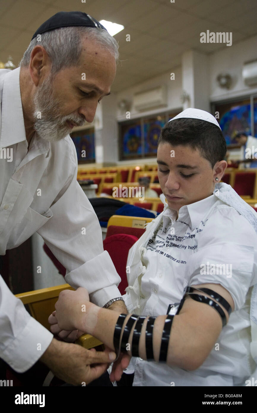 Bar Mitzvah boy laying tefillin (phylacteries) during ceremony - Stock Image