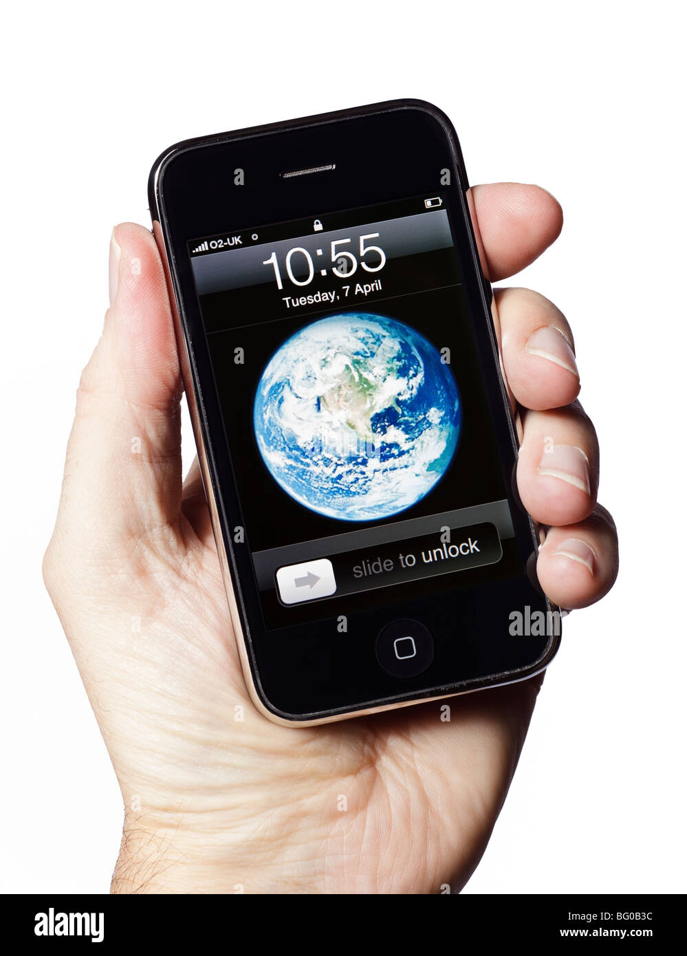 Male hand holding iPhone showing start screen, cut out - Stock Image