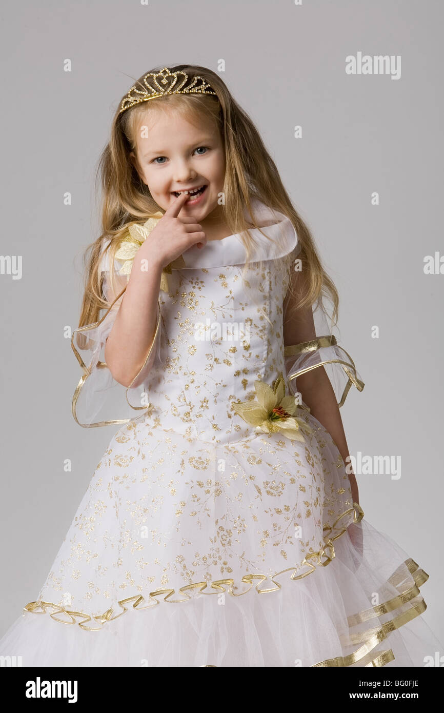 0febc54f25bd little beautiful girl in princess dress with long hair holds finger in  mouth and laughs on grey background