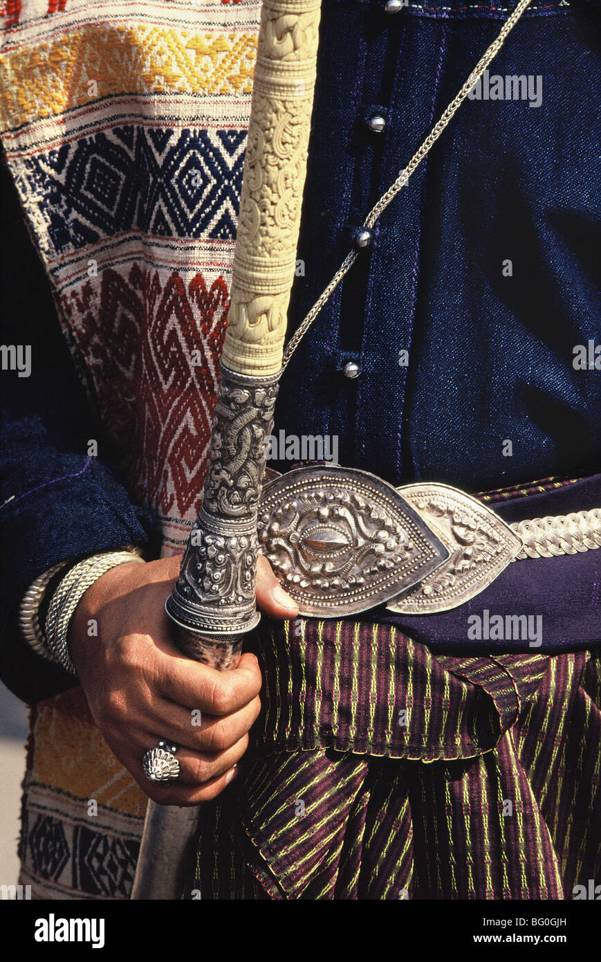 Lanna Silver Sword on a man wearing Tai Lu patterend sash over ceremonial dress, Northern Thailand, Southeast Asia, - Stock Image