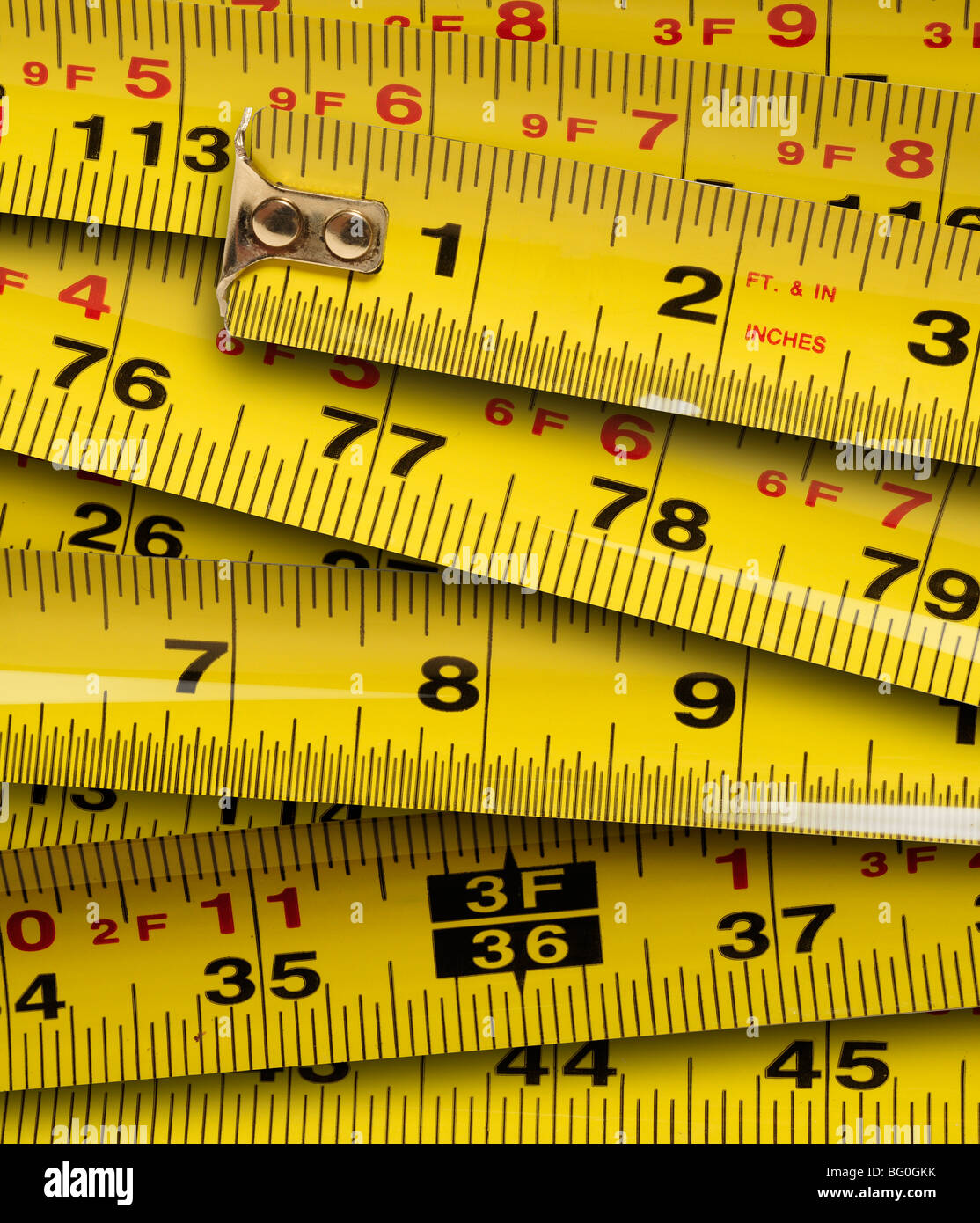Close up of metal yellow measuring tapes - Stock Image