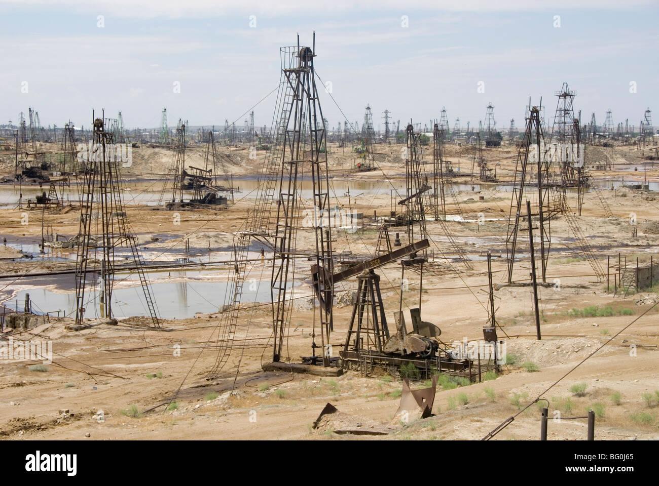 Closely spaced drilling towers and nodding donkey beam pumps, Ramana oilfield, Absheron peninsula, Baku, Azerbaijan - Stock Image