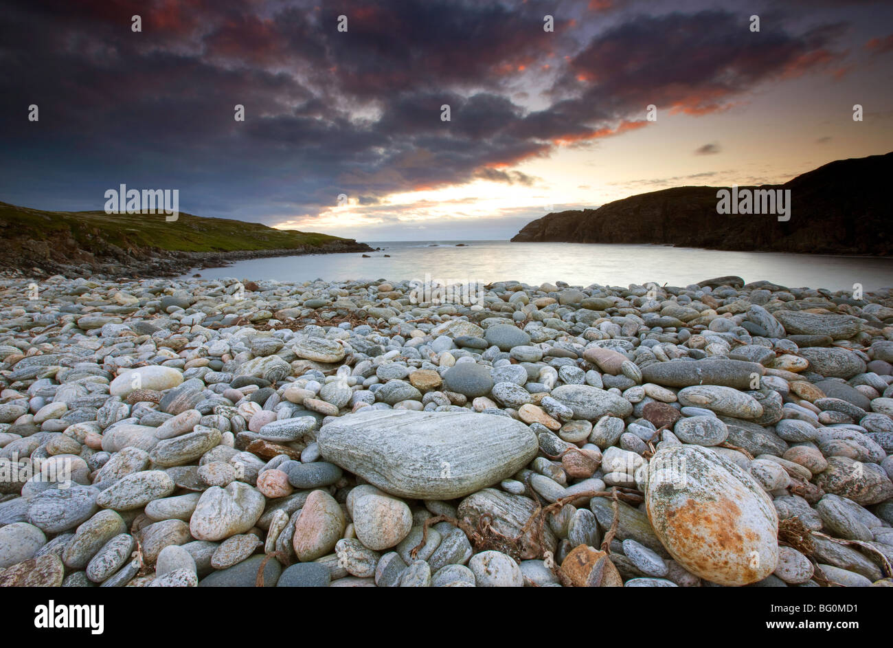 Looking out to sea at sunset across the rocky beach at Gearranin, Isle of Lewis, Outer Hebrides, Scotland, United - Stock Image