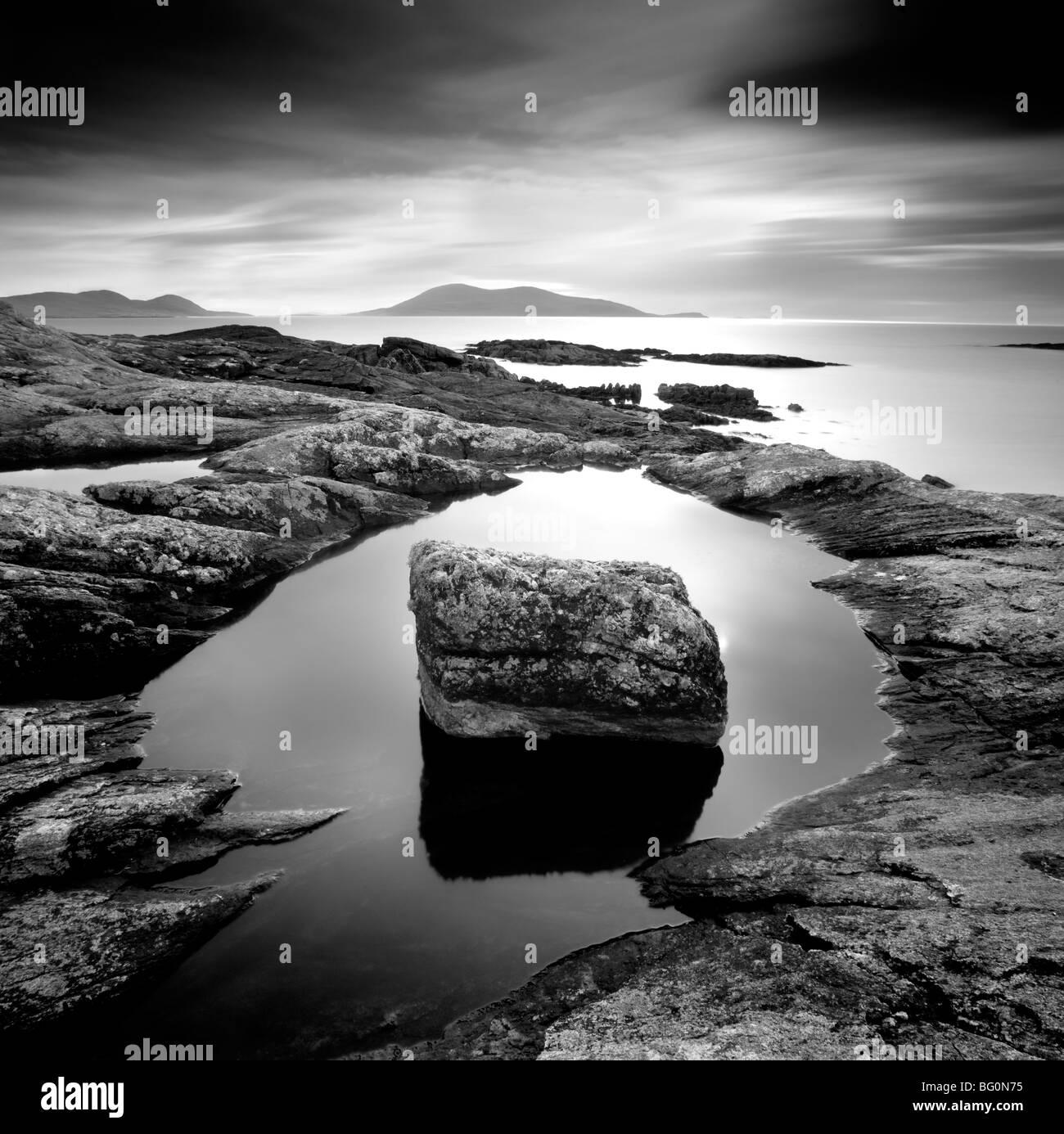 Erratic in tidal pool on isle of Taransay, looking towards Toe Head on South Harris, Outer Hebrides, Scotland, United - Stock Image