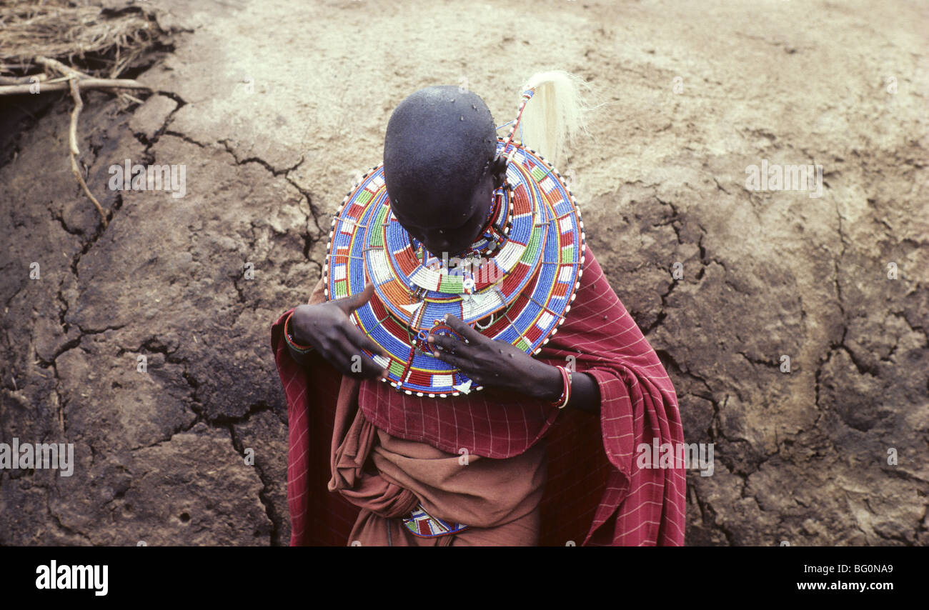 A Masai woman adjusts her beaded neck ware in front of her mud cow dung hut in Amboseli National Park, Kenya - Stock Image