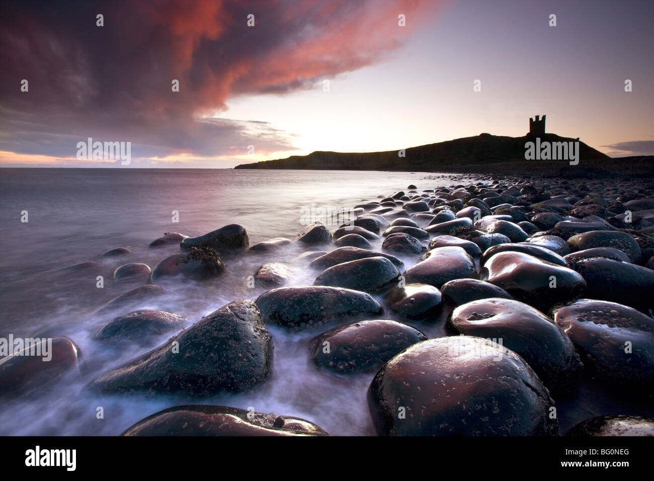 Dawn over Embleton Bay, basalt boulders in foreground and ruins of Dunstanburgh Castle in background, Northumberland, - Stock Image