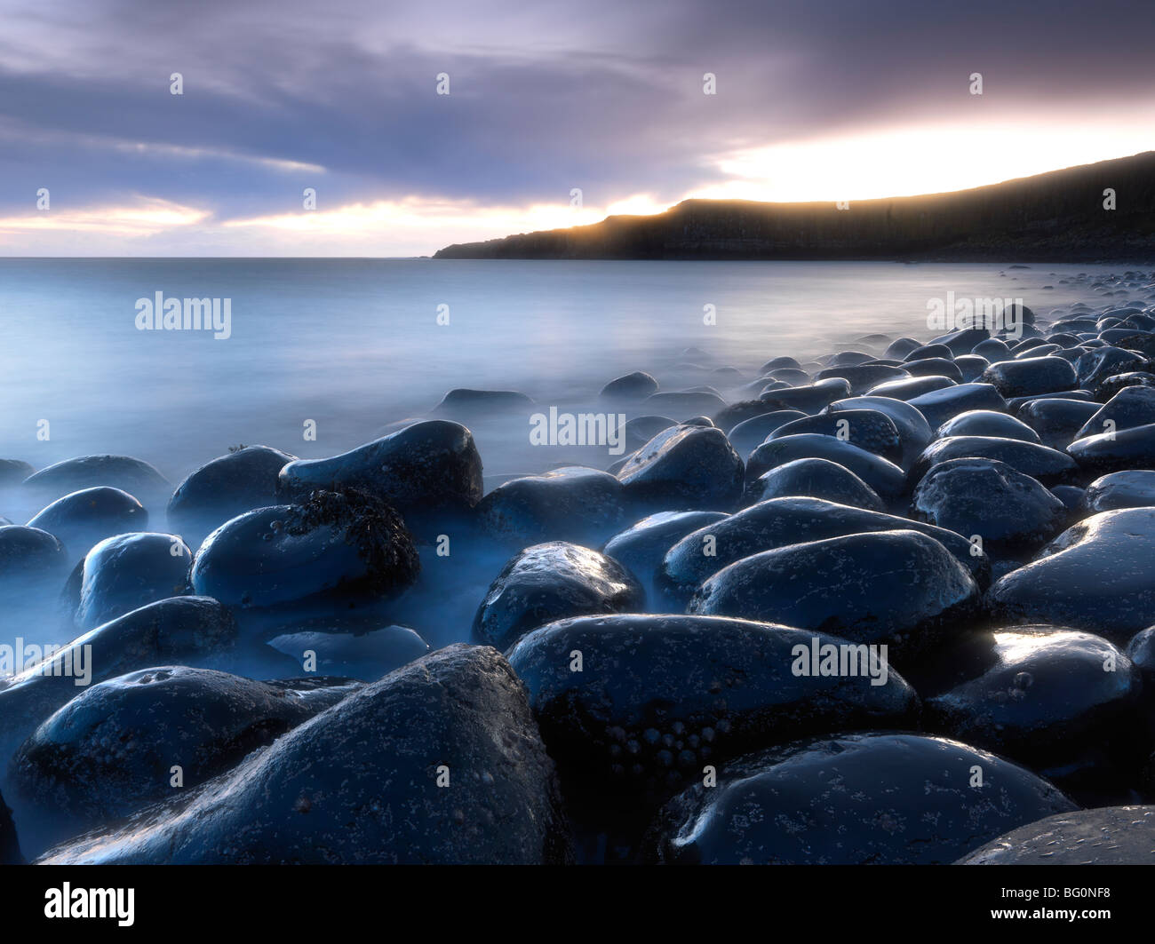Embleton Bay at dawn from beach of basalt boulders known as The Rumble Churn, Northumberland, England, United Kingdom Stock Photo