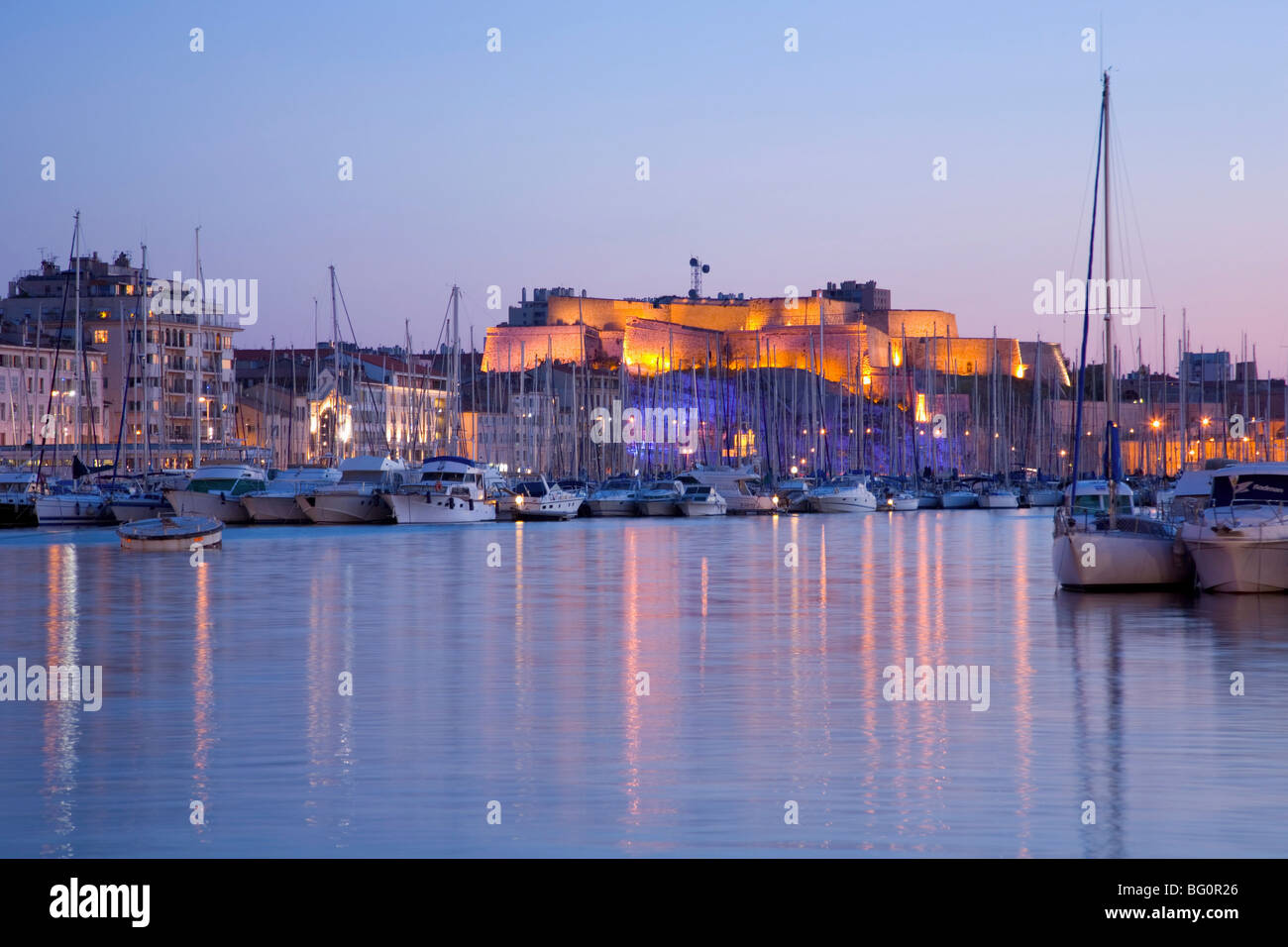 View across the Vieux Port to illuminated Fort St.-Nicolas at dusk, Marseille, Bouches-du-Rhone, Cote d'Azur, - Stock Image