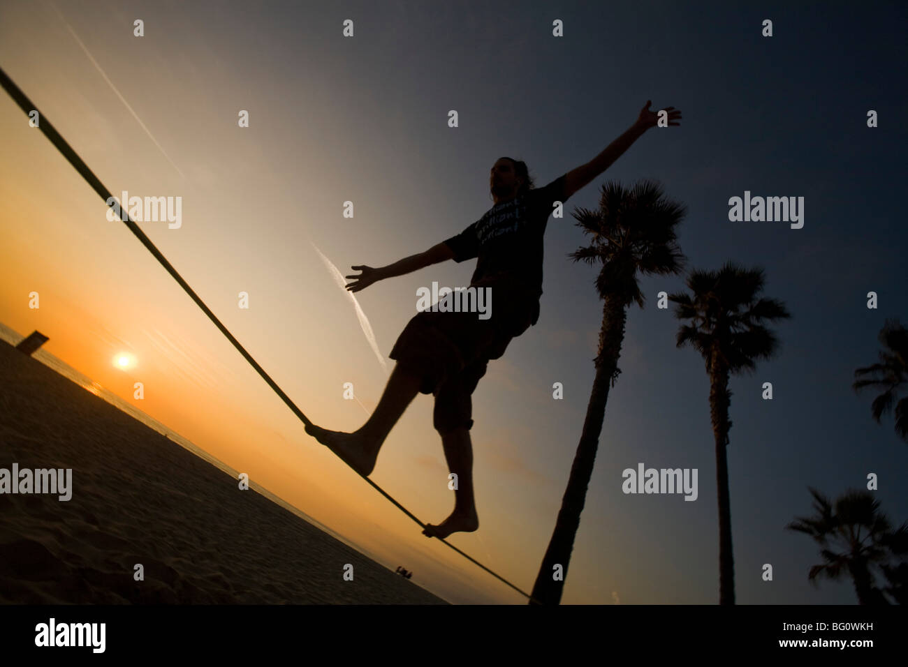 Slacklining - blanacing on a slackline - Venice Beach, Los Angeles County, California, United States of America - Stock Image