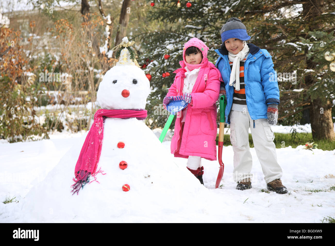 boy and girl next to snowman - Stock Image