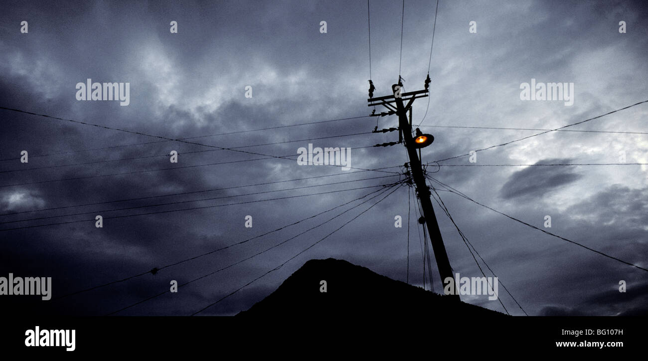 Telephone and electric power lines and street lamp at dusk in Santiago Atitlan, Guatemala - Stock Image