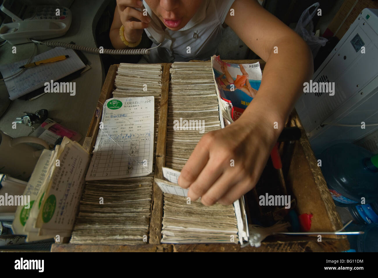 a girl on the phone taking orders for water deliver in Beijing, as she scans through index cards - Stock Image