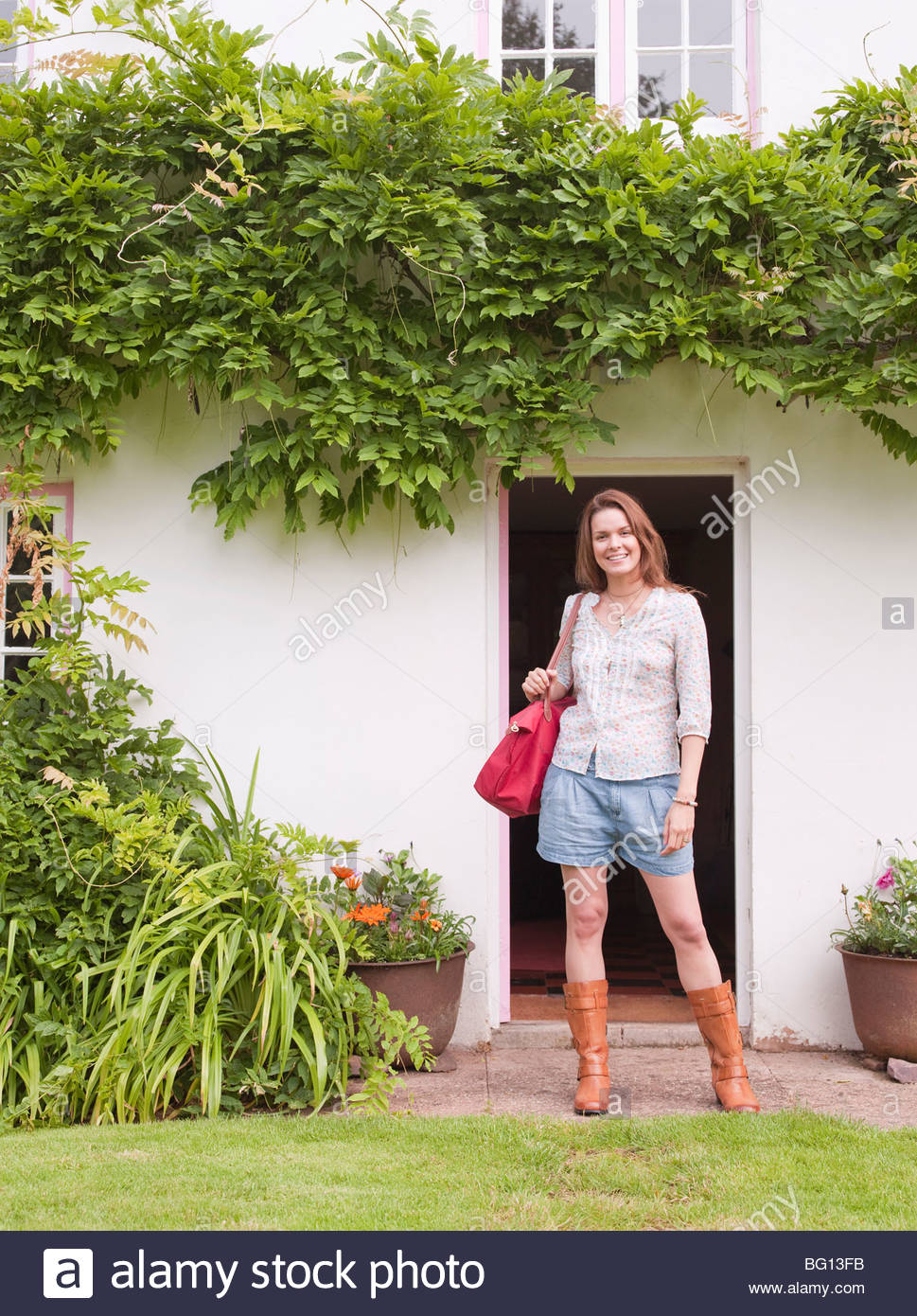 woman by front door of house - Stock Image