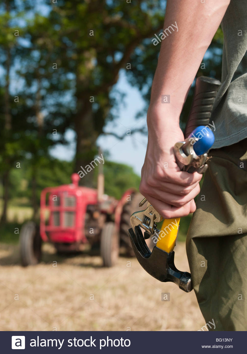 man holding tools by tractor - Stock Image