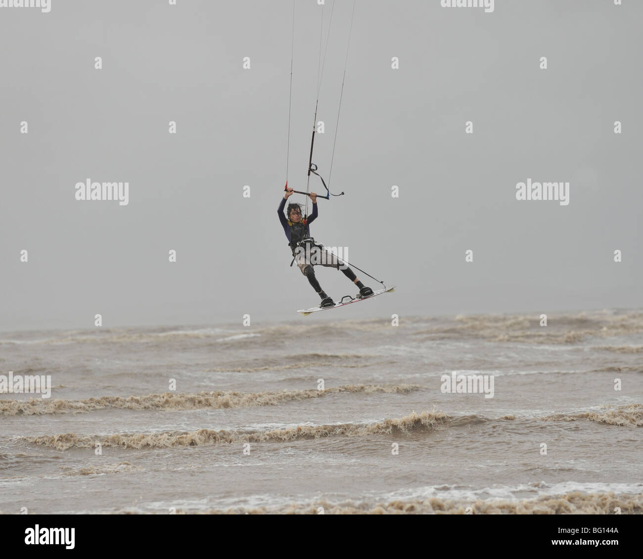 kite surfer leaping the waves - Stock Image