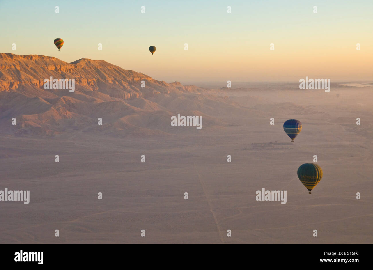 Hot air balloons flying over desert at dawn on the West bank of the river Nile near Luxor, Egypt, North Africa - Stock Image