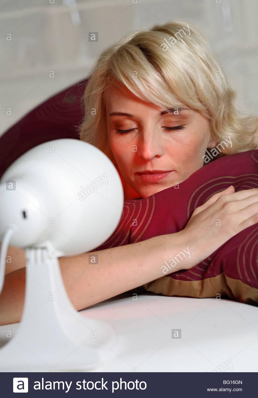 blond woman lying on sofa - Stock Image