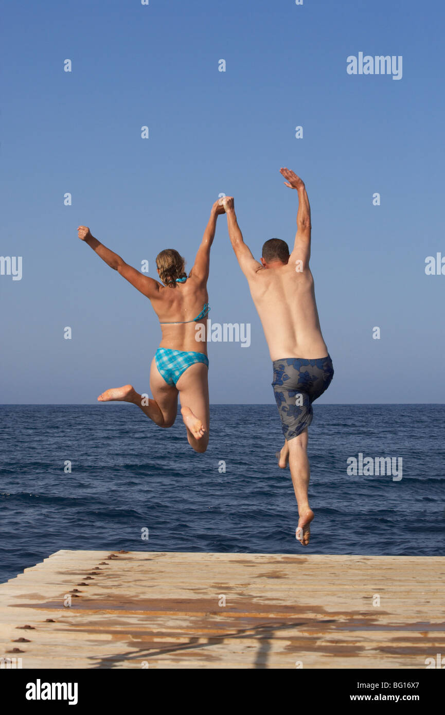 Man and Woman jumping into sea from pier Stock Photo