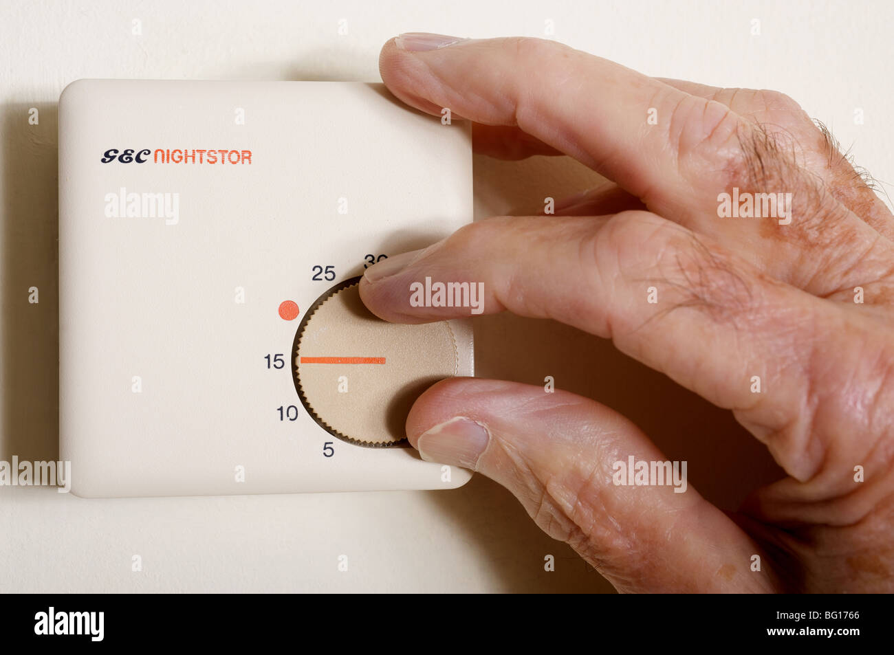 Old aged pensioner turning down the temperature control on his central heating thermostat - Stock Image