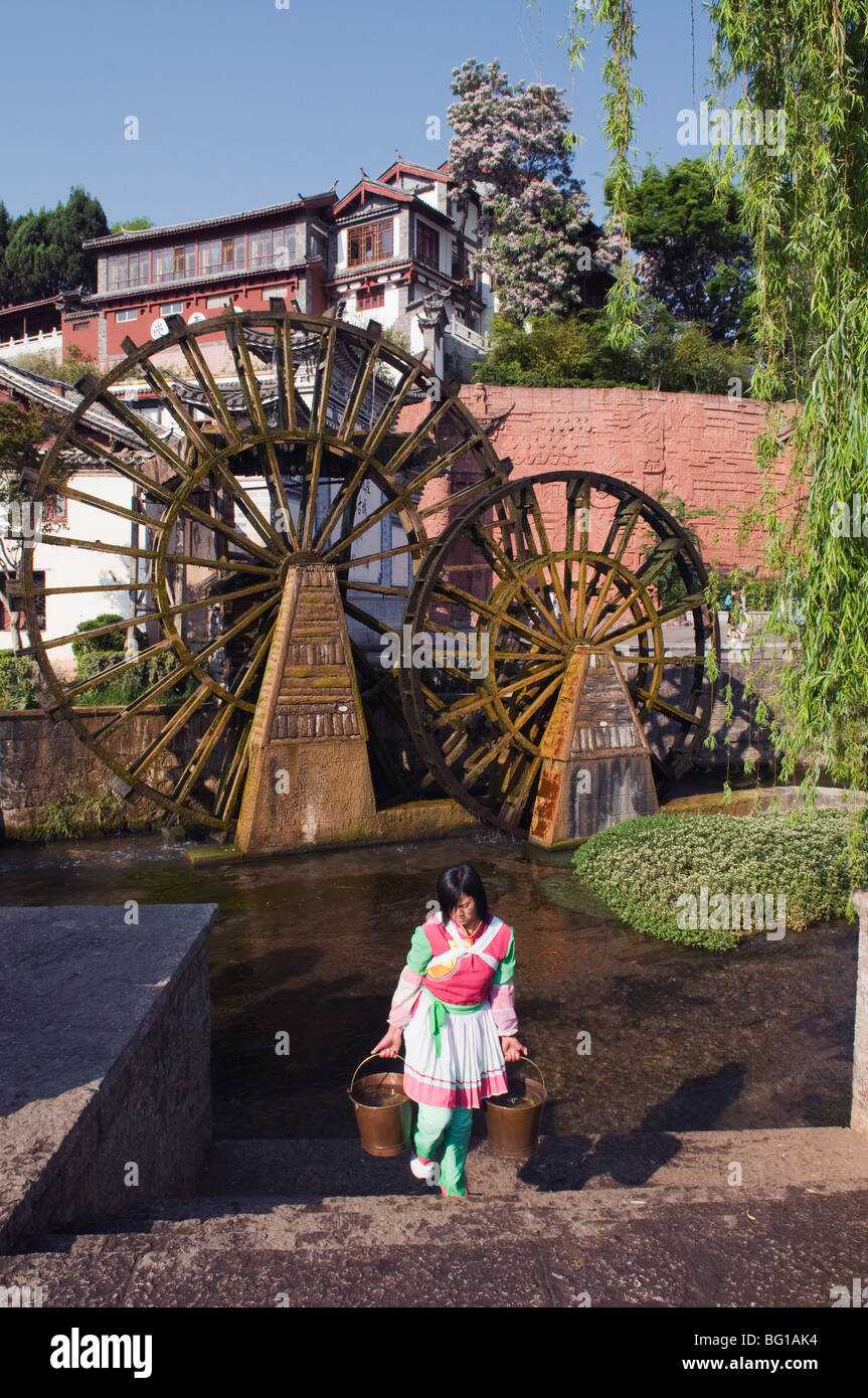 A Bai girl carrying buckets of water in front of a water wheel in Lijiang Old Town, UNESCO, Yunnan Province, China, - Stock Image