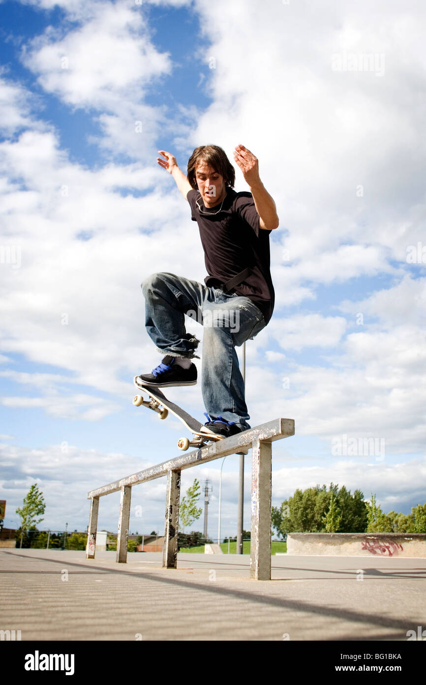 Skateboarder doing a crooked grind on rail - Stock Image