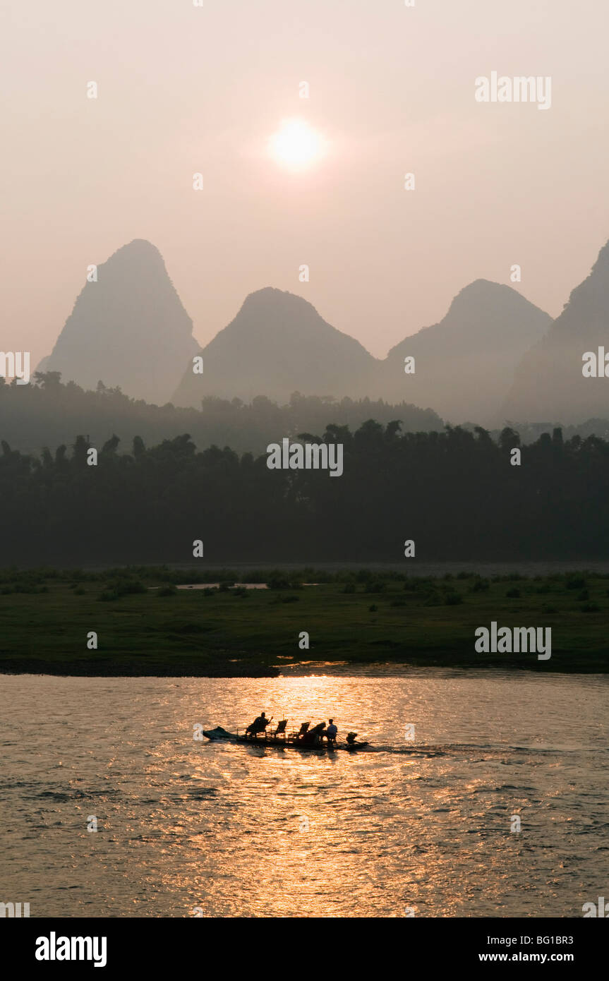 Tourist boat sailing through karst scenery at sunrise on the Li river (Lijiang) in Yangshuo, nr Guilin, Guangxi Stock Photo