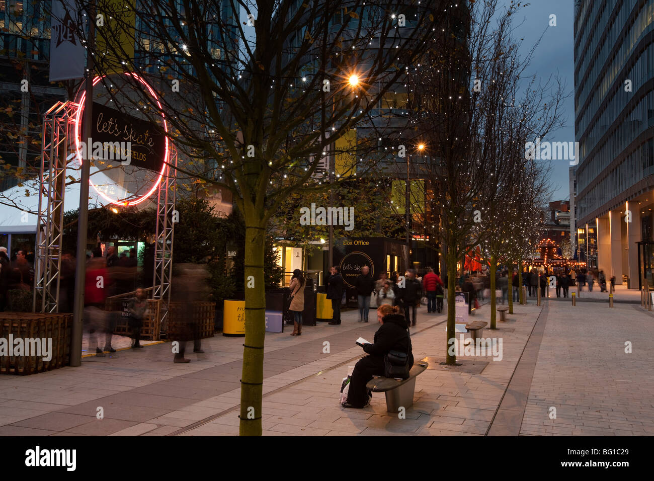 UK, England, Manchester, Spinningfields at night, visitors outside Christmas ice skating rink - Stock Image