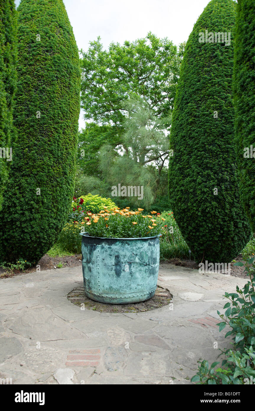A view of a pot in a garden with orange flowers - Stock Image