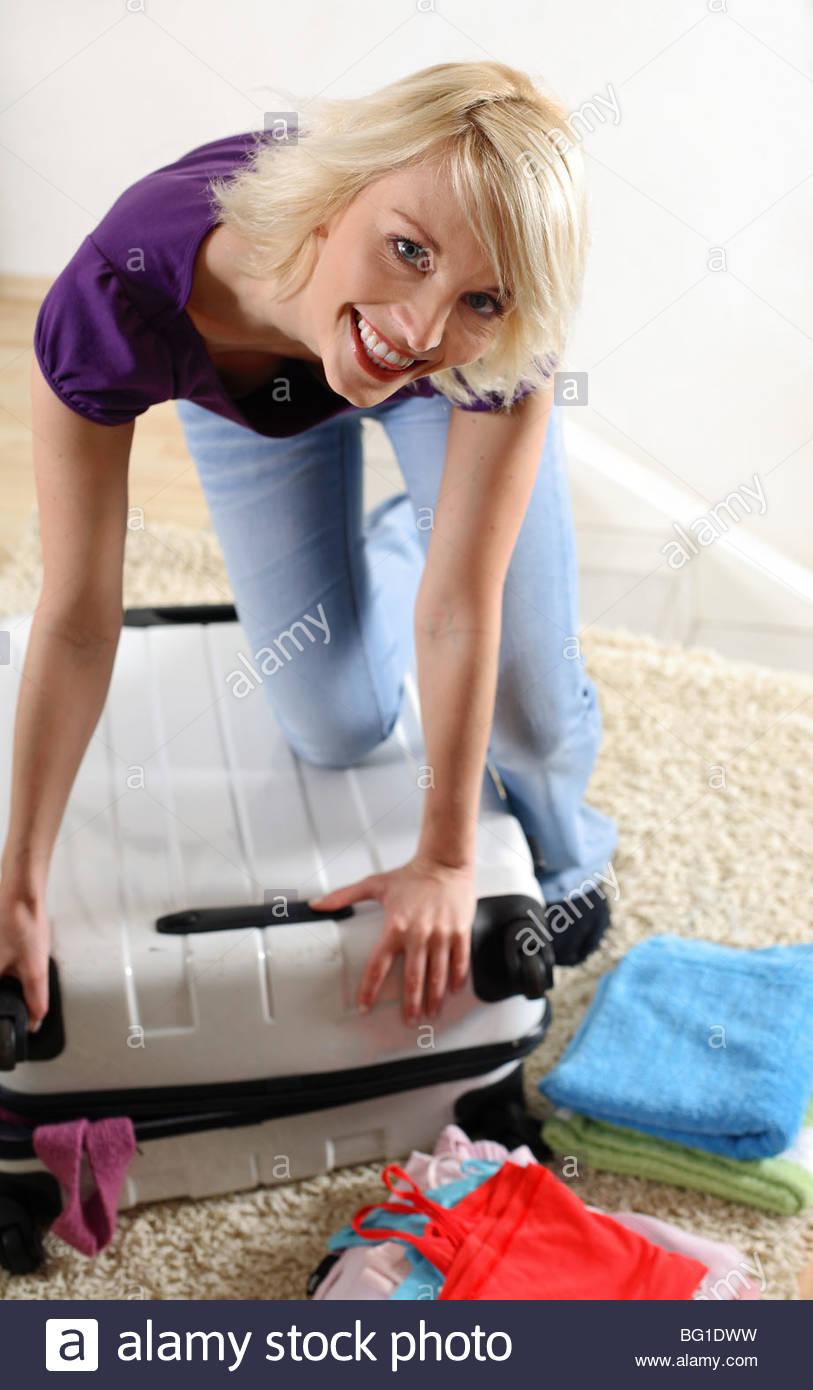 woman is packing her suitcase Stock Photo