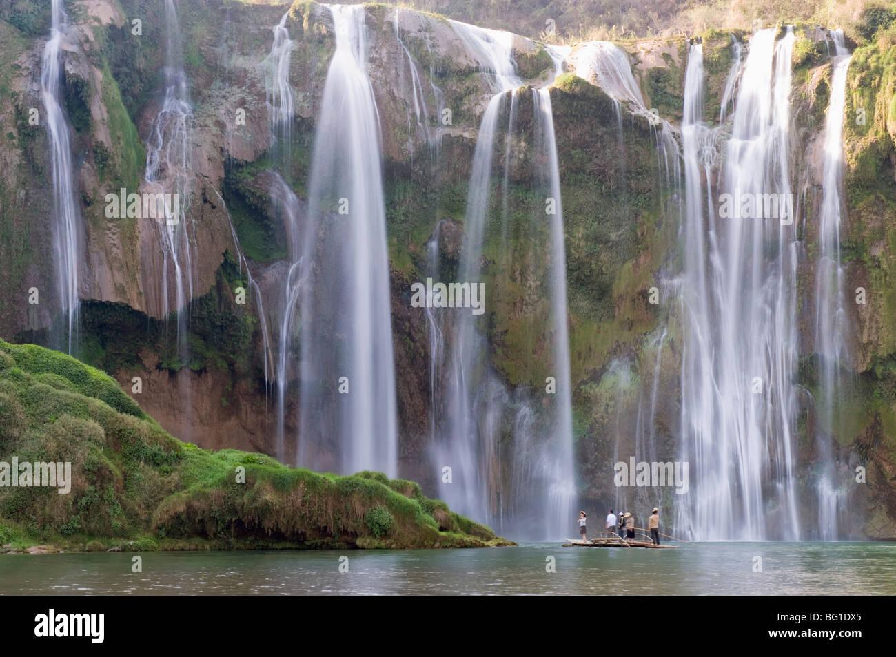 Tourists on a bamboo raft under Jiulong Falls (Nine Dragon waterfall), Luoping, Yunnan Province, China, Asia - Stock Image