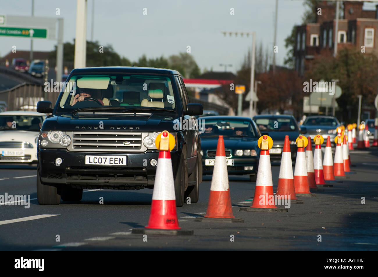 driver in 4 wheel drive speaking on mobile phone passes road works and traffic cones - Stock Image