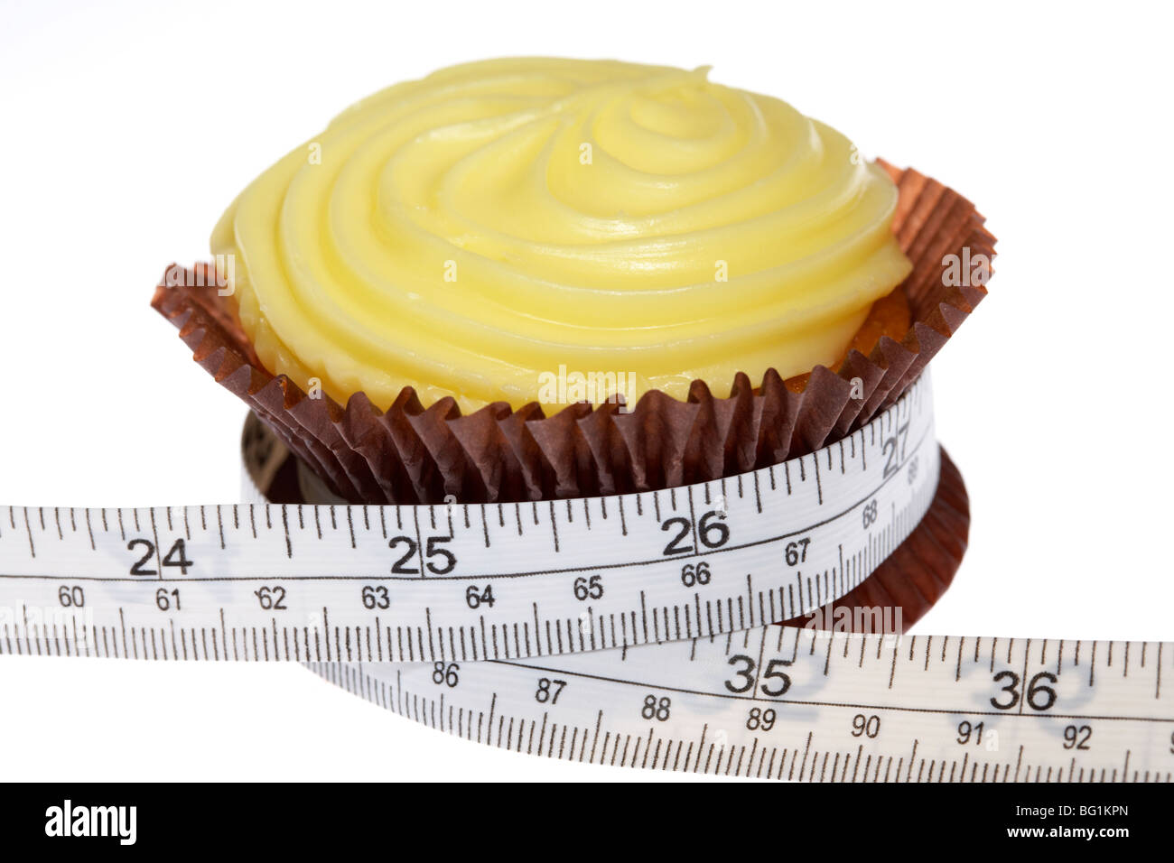 yellow cupcake with frosted icing squeezed by measuring tape with metric and imperial measurements Stock Photo