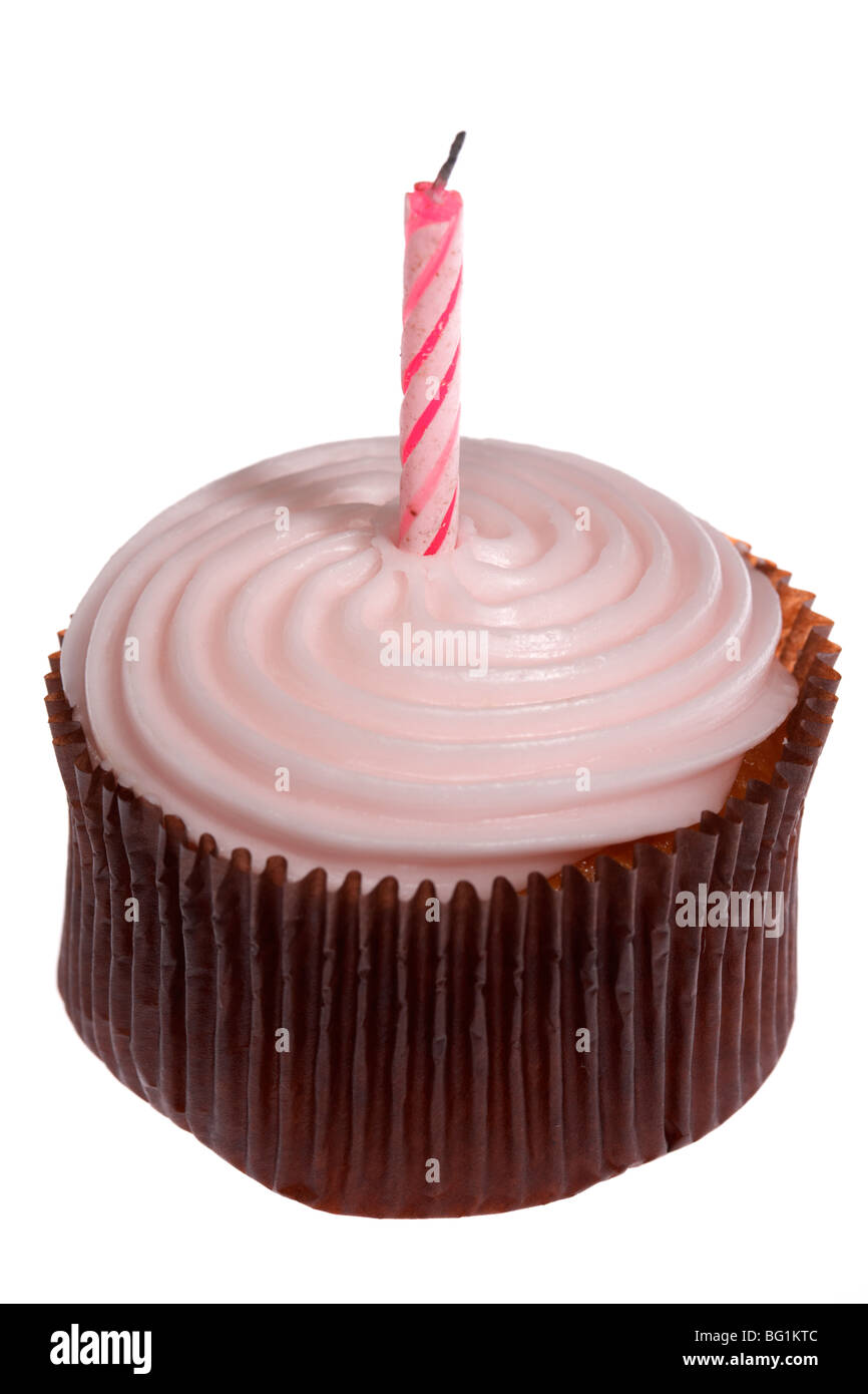 pink cupcake with frosted icing and single blown out birthday candle - Stock Image