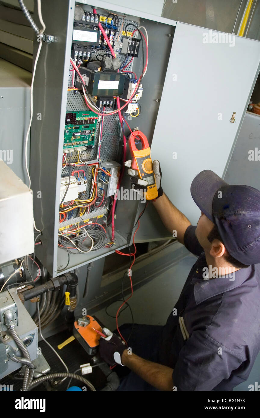 Worker testing voltage on a buildings environmental control box. - Stock Image