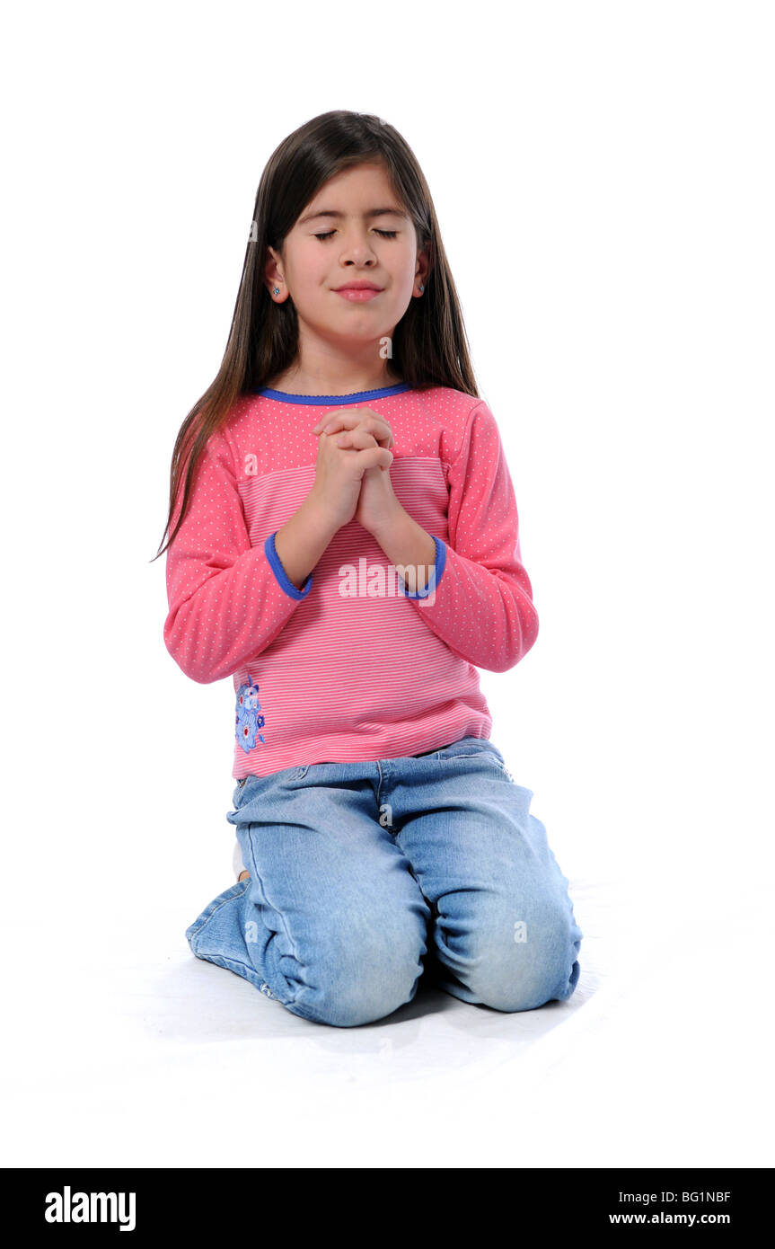 Young girl with hands clasped together praying - Stock Image