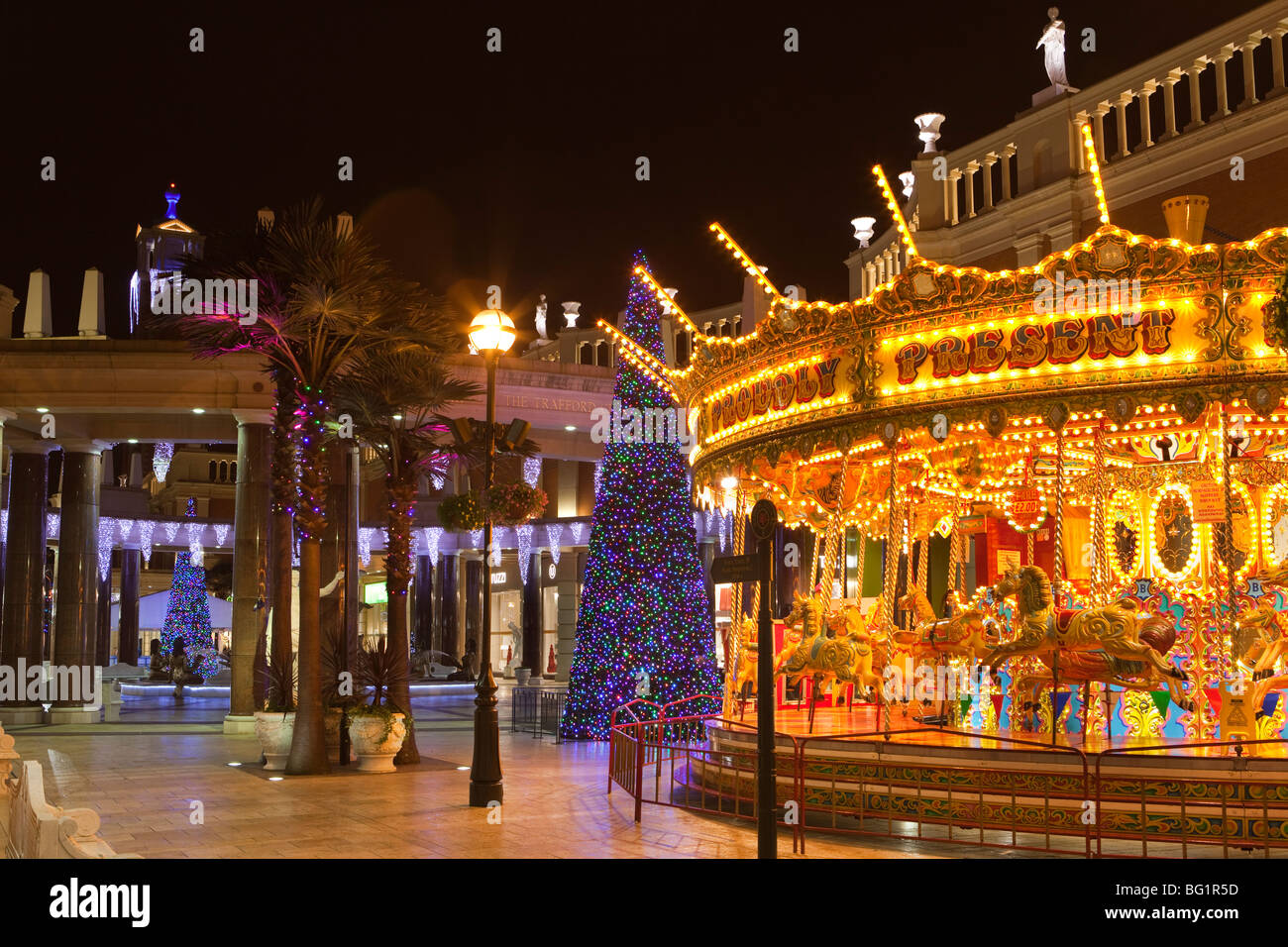 UK, England, Manchester, Trafford Centre shopping mall, Barton Square, traditional carousel and Christmas tree - Stock Image
