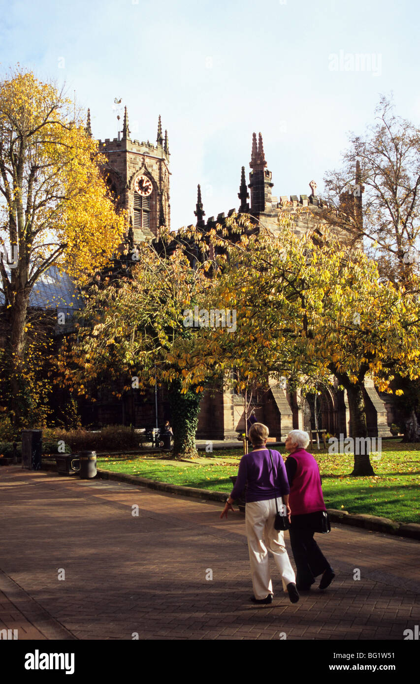 Two Elderly Ladies Walking In Nantwich Town Centre In Cheshire Near To St Mary's Church - Stock Image