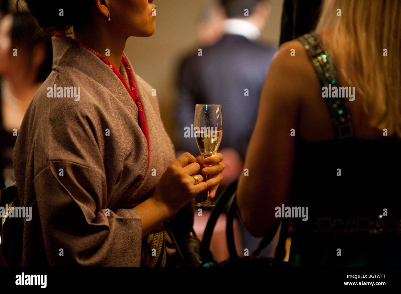 Japanese woman in kimono drinking champagne. - Stock Image